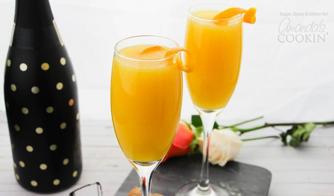 Mimosas in champagne flutes with orange twist garnish