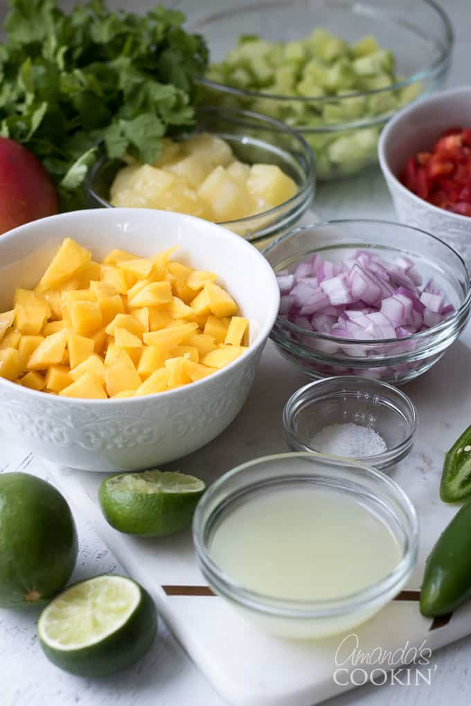 mangoes, cucumber, red bell pepper, pineapple, cilantro and jalapeno in bowls