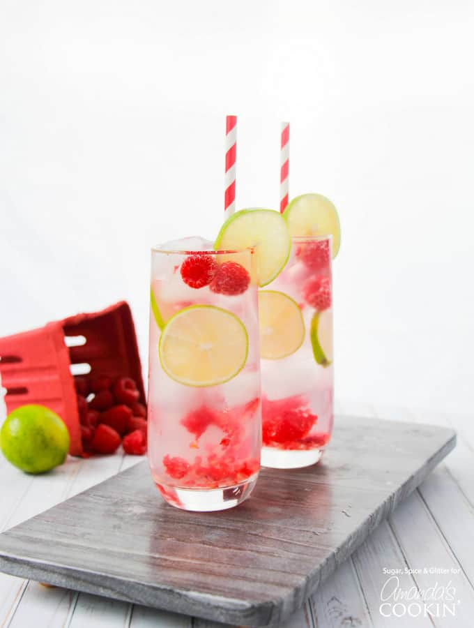 cocktail in glass with paper straws, lime, and raspberries