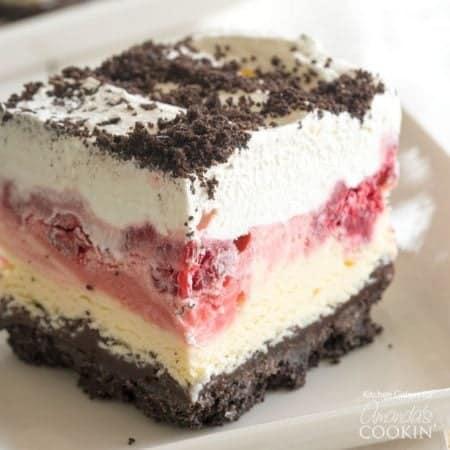 This raspberry ice cream delight cake has layers of vanilla ice cream with raspberries, hot fudge and whipped cream on an Oreo cookie crust!