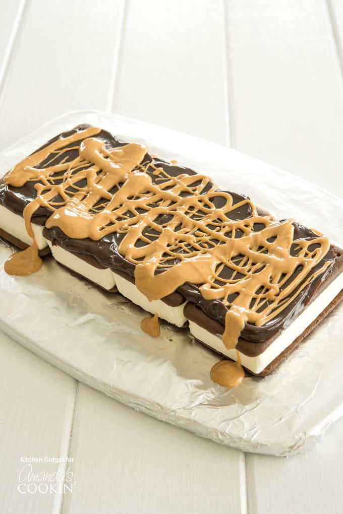 A photo of a layer of hot fudge sauce and melted peanut butter drizzled over a layer of ice cream sandwiches.
