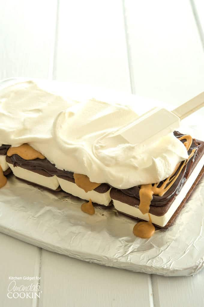 Add a layer of whipped topping to ice cream sandwiches with hot fudge and peanut butter drizzle