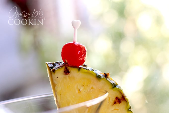 pineapple wedge and maraschino cherry on side of glass