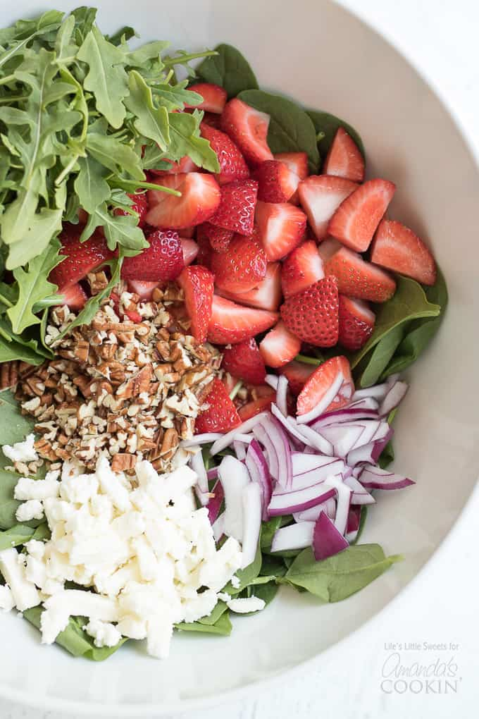 Strawberries, red onions, pecans and spinach in a mixing bowl for strawberry salad.
