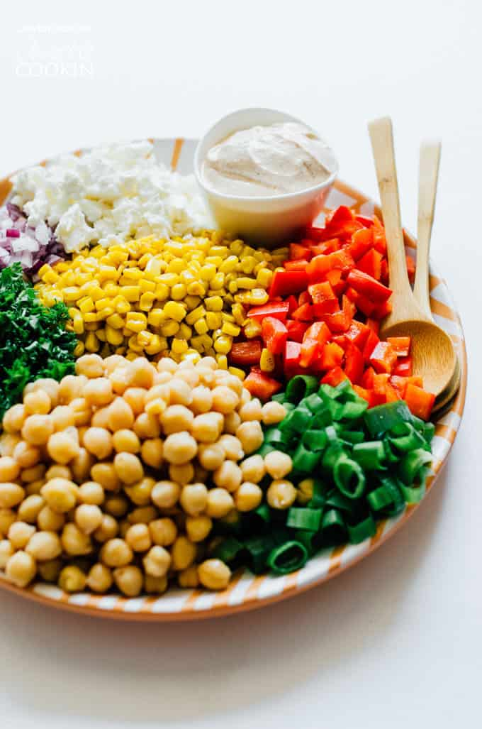 sweet corn and chickpea salad with dressing and spoons