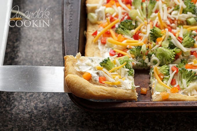 serving appetizer veggie pizza with spatula