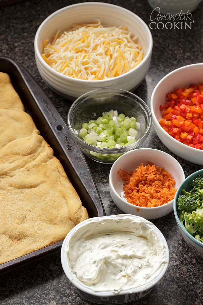 crescent dough with bowls of vegetables and cheese