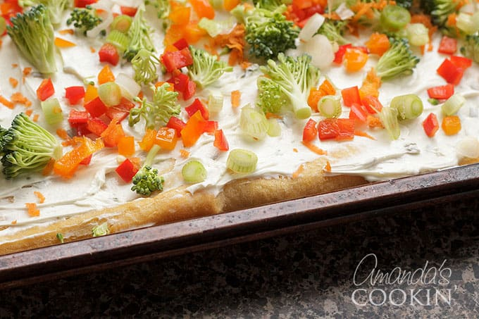 fresh vegetables on top of cream cheese layer
