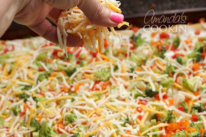 adding shredded cheese to appetizer veggie pizza