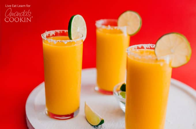 Mango Margarita Slush in glasses with a salted rim and lime garnish.