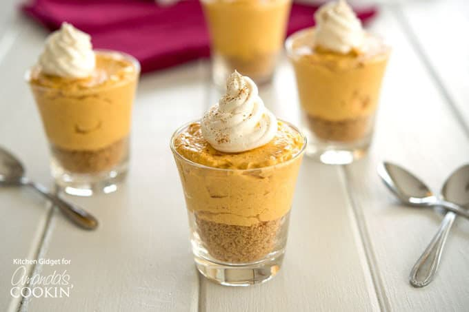 Mini no bake pumpkin cheesecake in glasses with whipped topping.