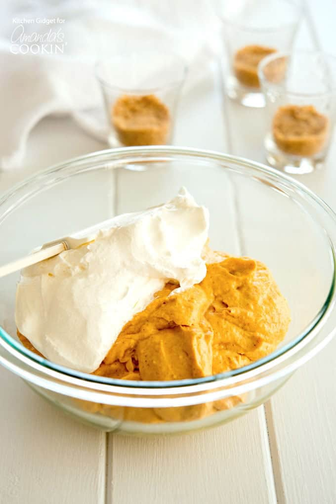 Folding in whipped topping with the no bake pumpkin cheesecake ingredients