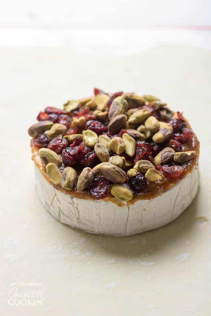 Brie cheese with fruit, nuts, and jam