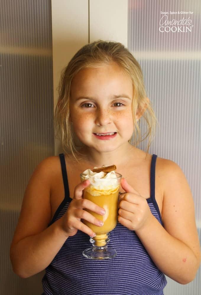 Girl holding pumpkin spice hot chocolate in a mug