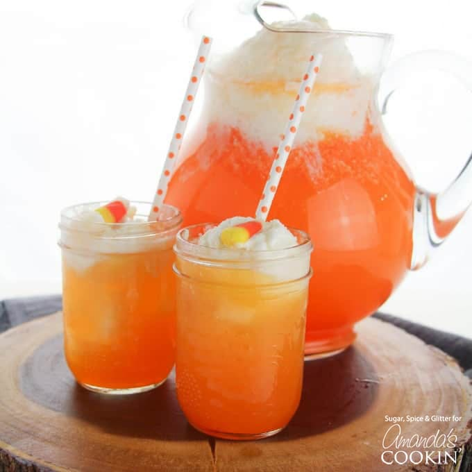two glasses of candy corn punch with pitcher in background
