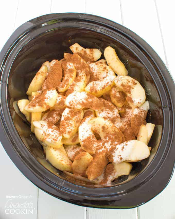 Making crockpot cinnamon apples, adding sugar and cinnamon.
