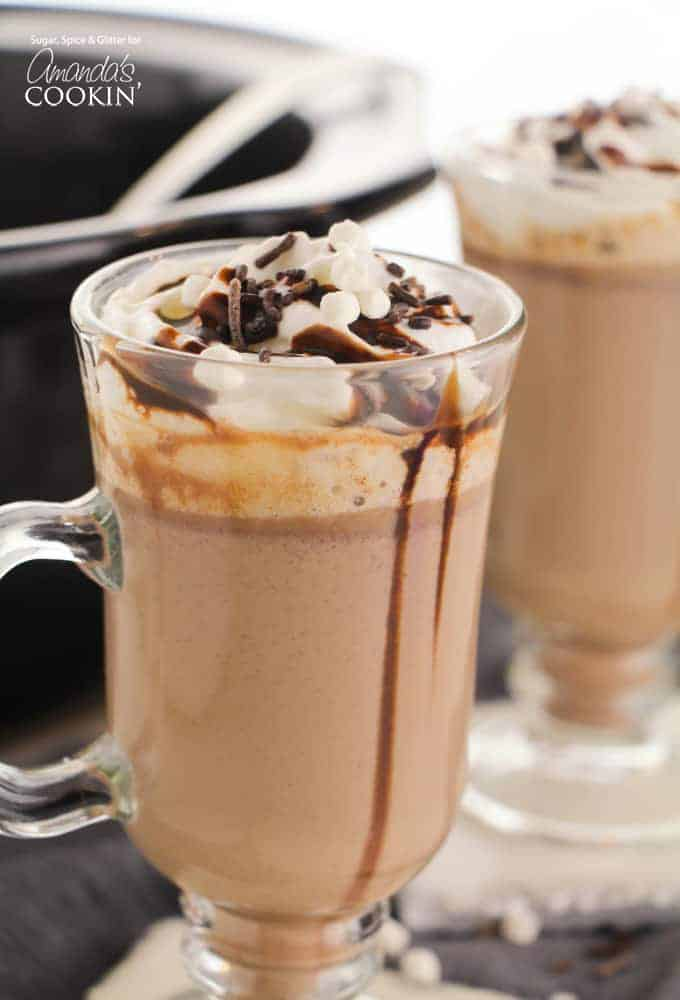 Creamy crockpot hot chocolate in a mug with chocolate sauce and marshmallows