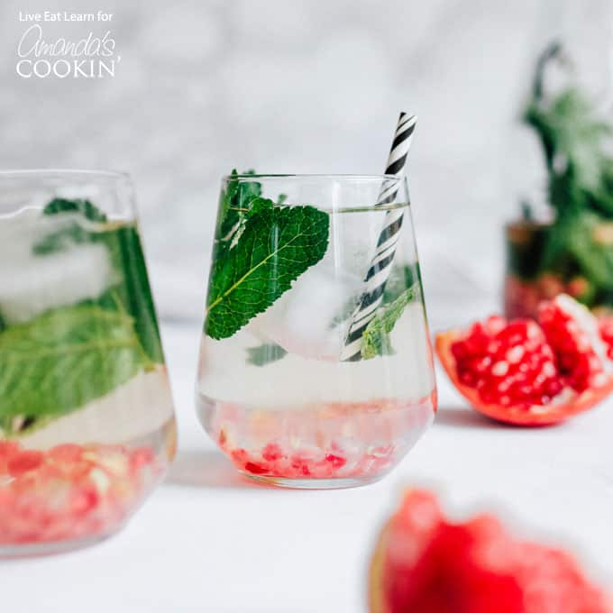 holiday detox drink in wine glass with fresh mint sprigs and cranberry seeds
