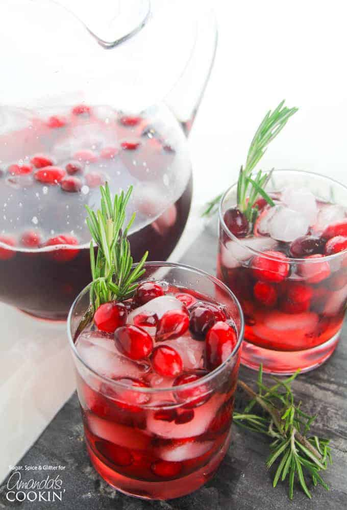 Cranberry Holiday Punch in cups with rosemary sprig garnishes