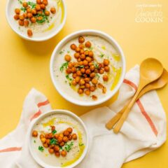 three bowls of cauliflower soup with chickpea garnish