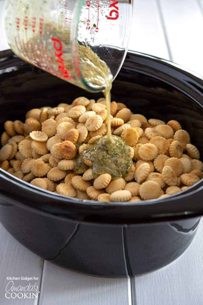 Ranch Seasoned Oyster Crackers- pouring seasoning over crackers