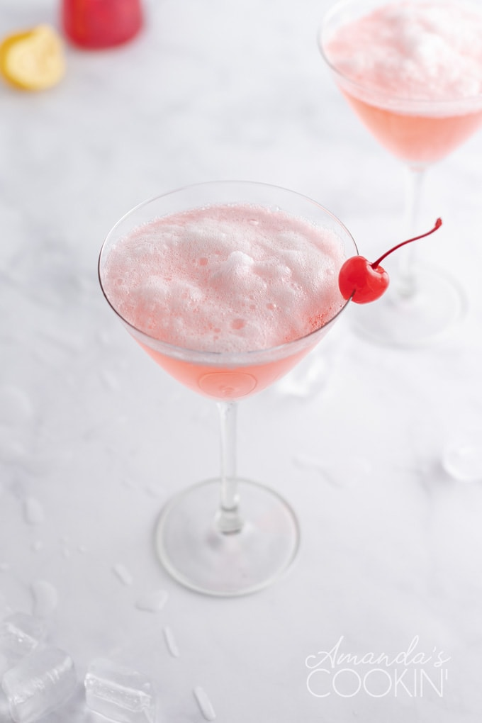 overhead view of frothy pink lady in martini glass