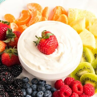 bowl of cream cheese fruit dip with fruit on a plate