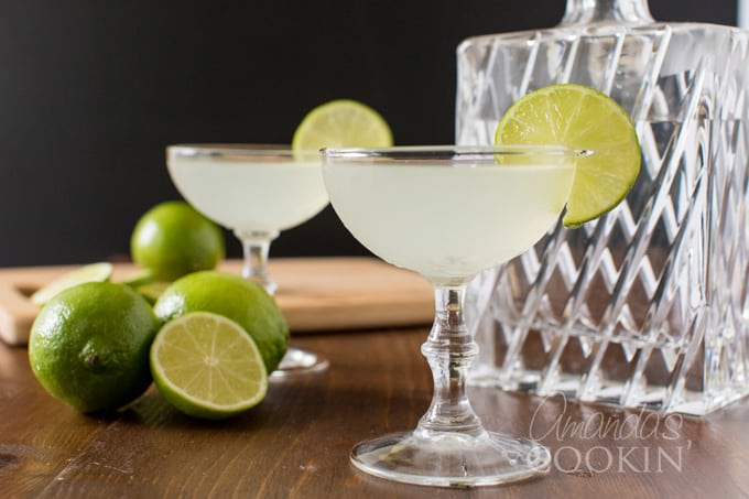 Two gimlets in coupe glasses garnished with lime wheels