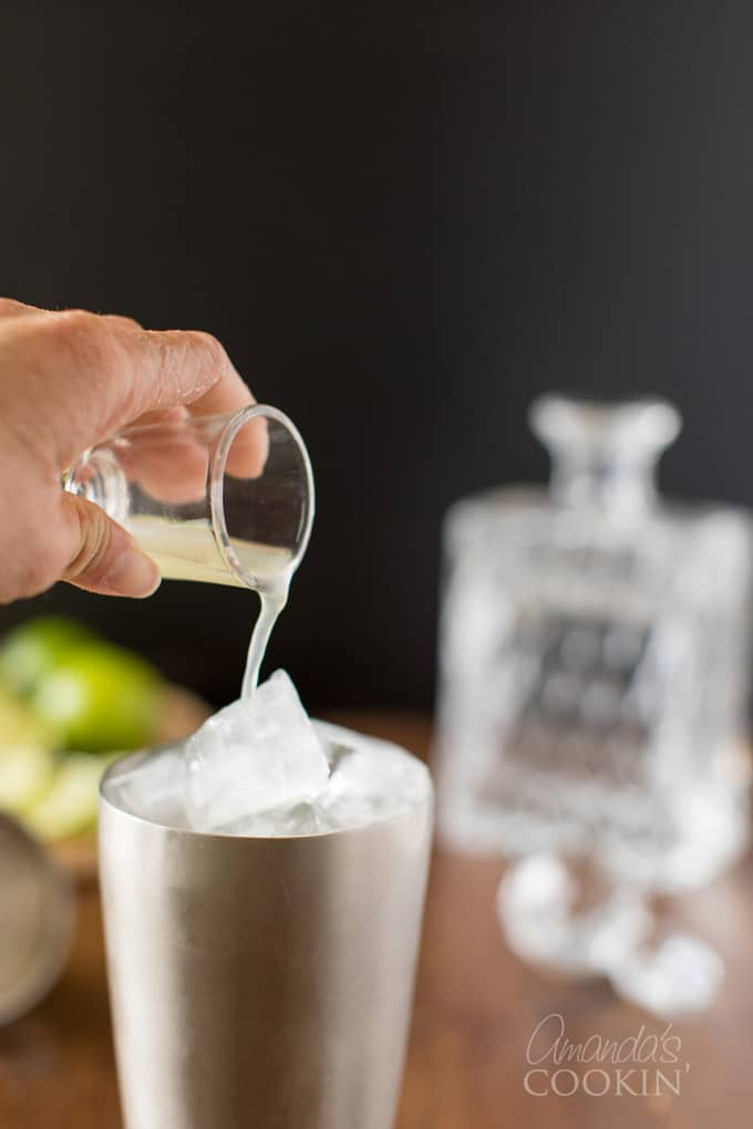 pouring lime juice into cocktail shaker