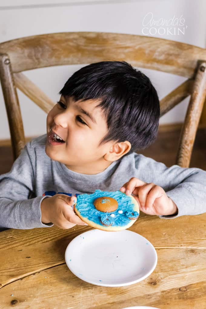 little boy eating bear cookie
