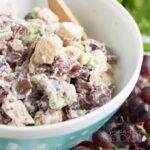 A close up of a bowl of chicken salad with grapes