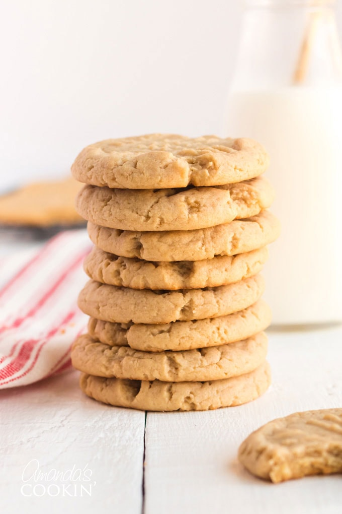 peanut butter cookies stacked with a bottle of milk