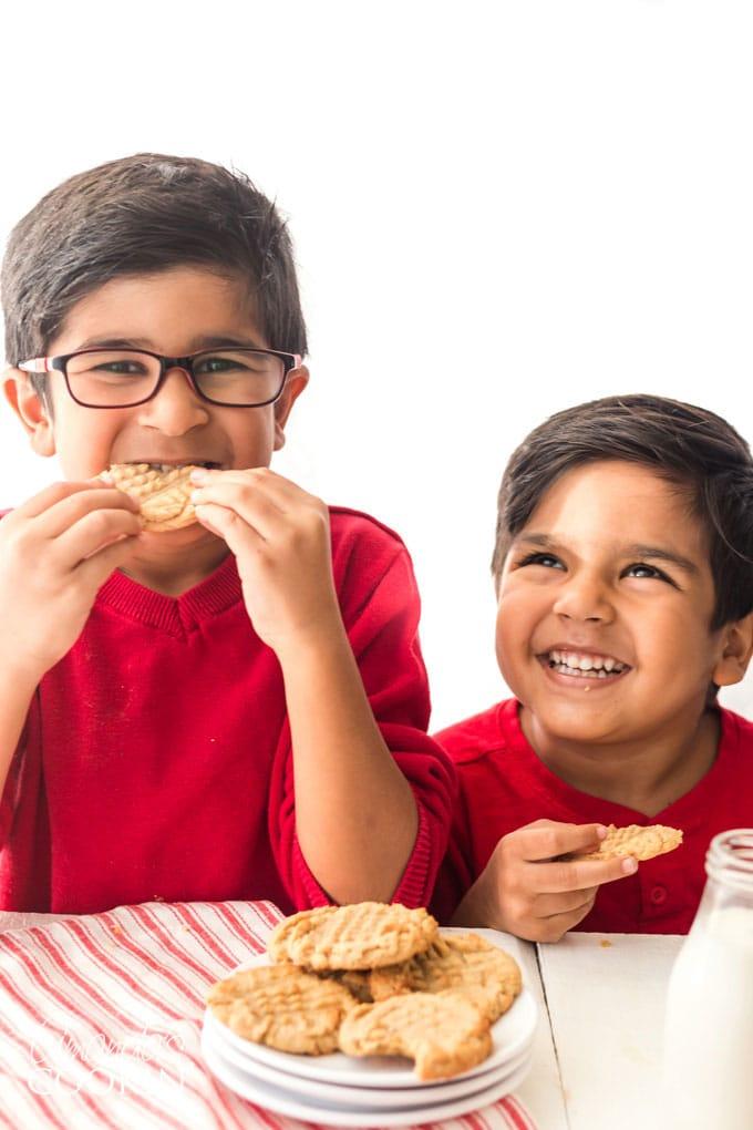 two cute kids eating peanut butter cookies