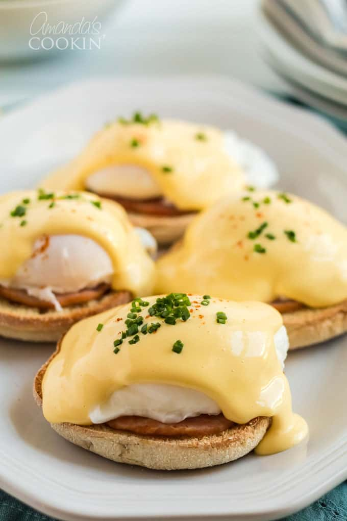 four servings of eggs benedict on a plate