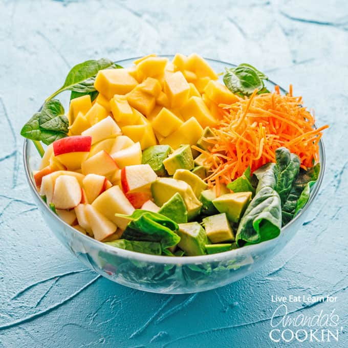 Spinach salad with avocado, mango, carrots and apples in a bowl