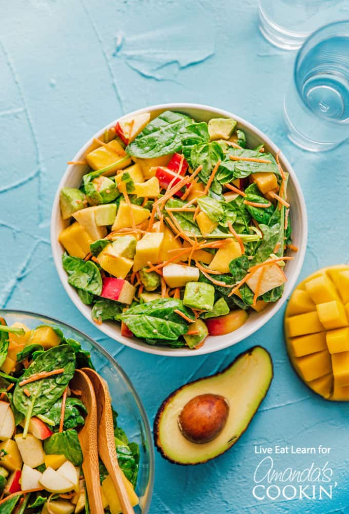 Spinach salad overhead shot with avocado, mango and apple