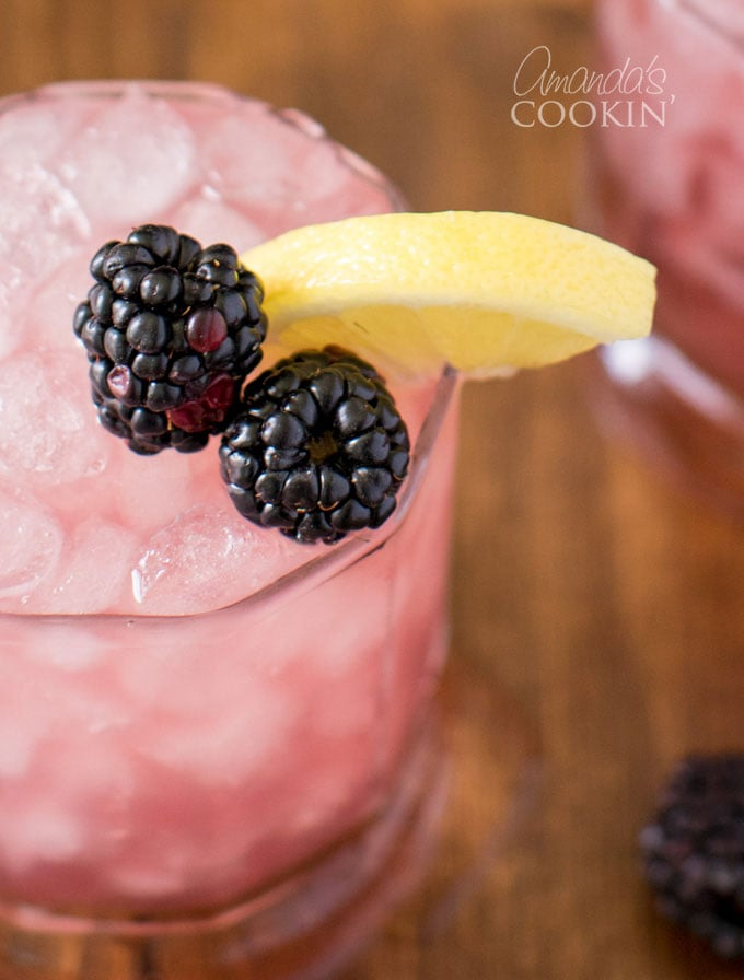 close up of bramble cocktail with blackberries and lemon on side of glass