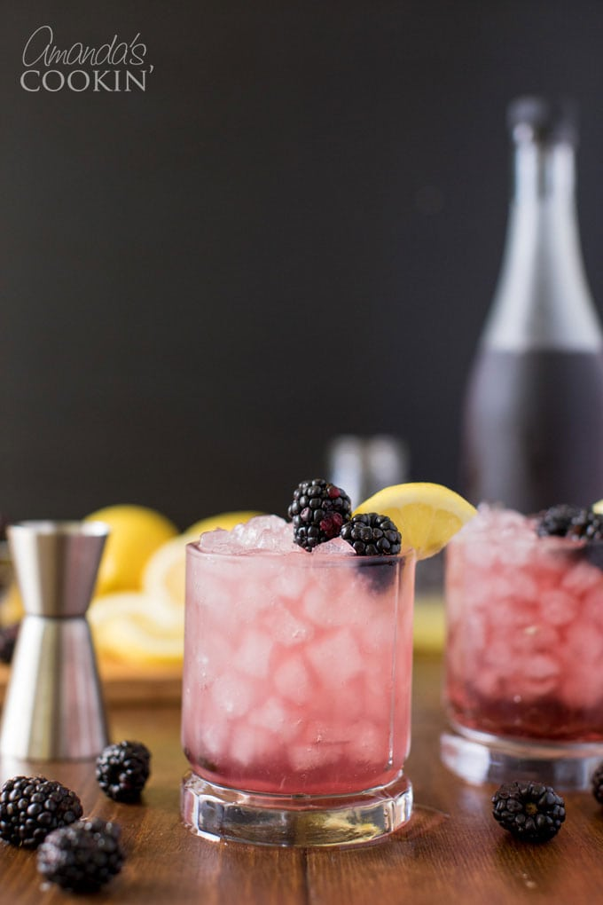 glass of bramble cocktail with blackberry and lemon garnish