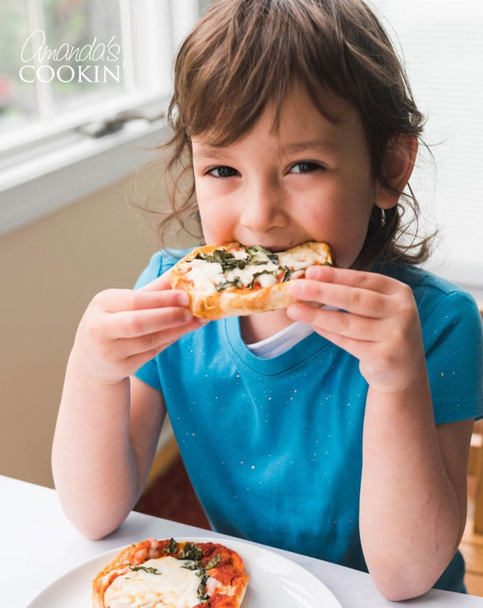 little girl taking bite from english muffin pizza