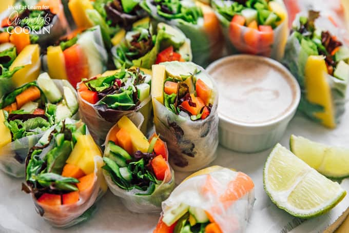 Vegetable spring rolls with dipping sauce and lime wedges