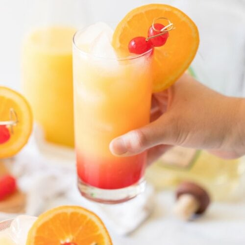hand holding a tequila sunrise cocktail