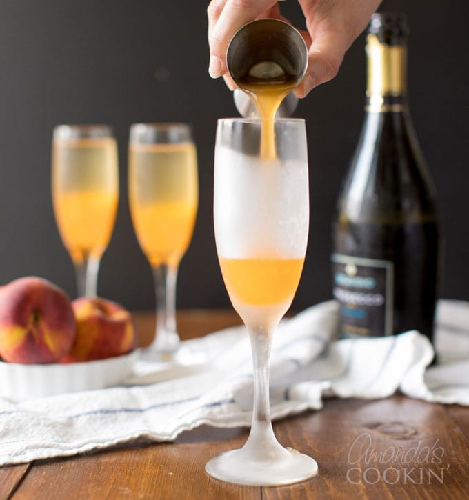 pouring peach puree into a champagne flute
