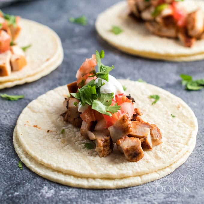 two corn tortillas with chicken taco filling and toppings