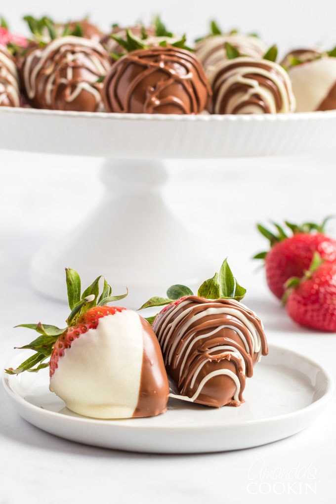 two chocolate covered strawberries on a plate with a cake plate in the background