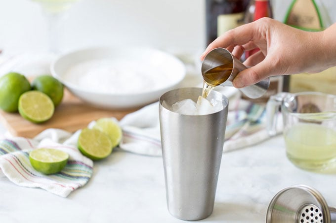 adding orange liqueur to cocktail shaker