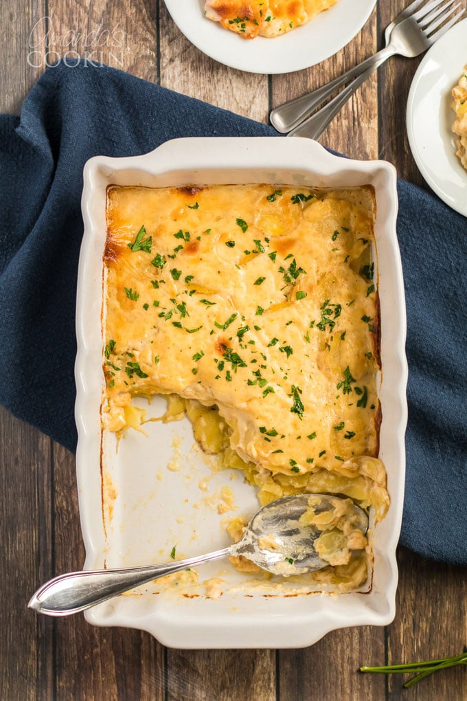 overhead shot pan of scalloped potatoes with some servings removed, spoon in pan