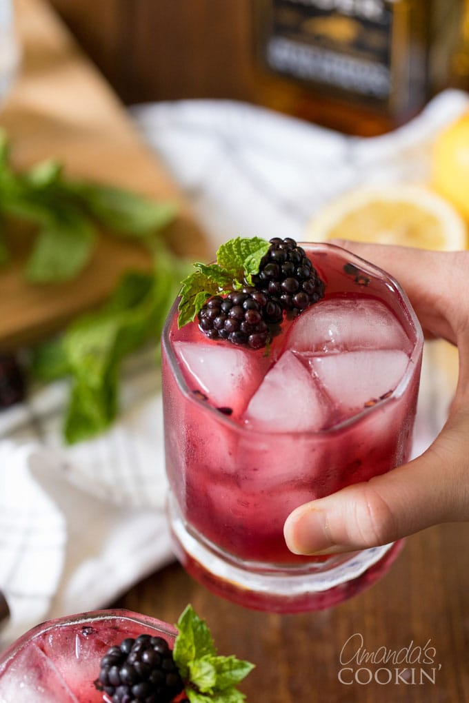hand holding a glass of blackberry lemonade with whiskey