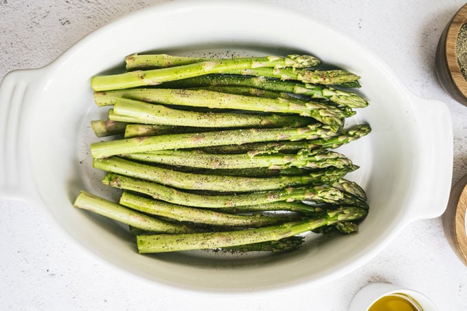 asparagus in a dish with salt and pepper in dishes around it