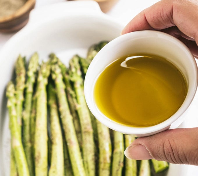 hand holding dish of olive oil with asparagus in the background