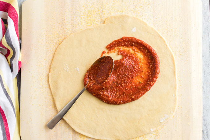 spreading sauce on pizza dough